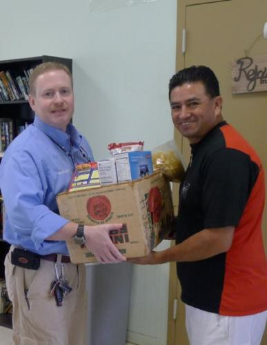The Chaplain giving away a box of food and canned goods.